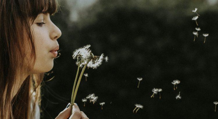 Frau pustet eine Pusteblume.