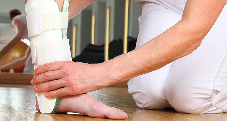 Eine Ärztin bandagiert einen verletzten Knöchel.