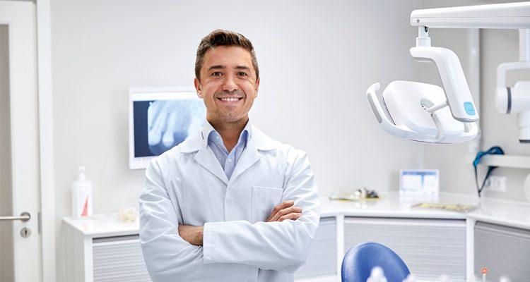 Arzt steht mit verschränkten Armen im Behandlungszimmer und lächelt