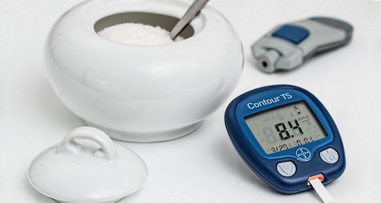 Ein Blutzuckermessgerät neben einem Topf Zucker.