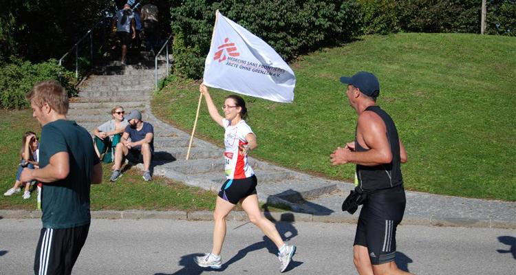 Frau in Läuferdress hält Flagge von Ärzte ohne Grenzen.