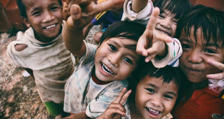 Lachende Kinder zeigen das Peace-Zeichen.