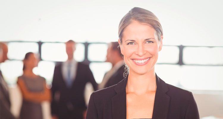 Frau lächelt in die Kamera, im Hintergrund Personengruppe unscharf