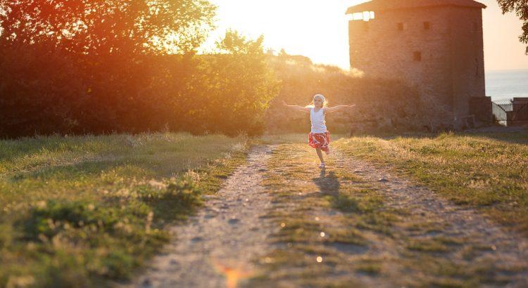 Blondes Mädchen tanzt vor Burg, hinter der die Sonne dezent scheint