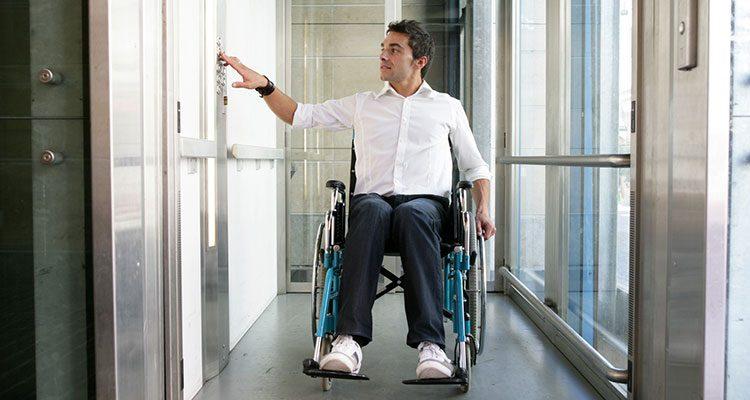 Mann im Rollstuhl in einem Aufzug.