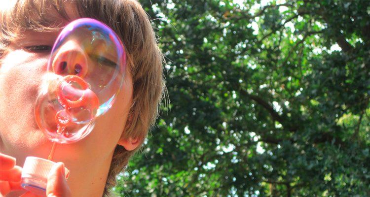 Junge pustet Seifenblasen, im Hintergrund Bäume im Sonnenschein