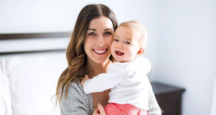 Glückliche Mutter hält lächelndes Baby auf dem Arm, erfüllter Kinderwunsch