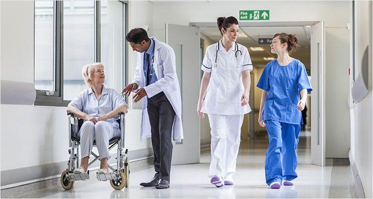 Ärzte, Krankenschwestern und eine Rollstuhlfahrerin auf dem Gang in einem Krankenhaus