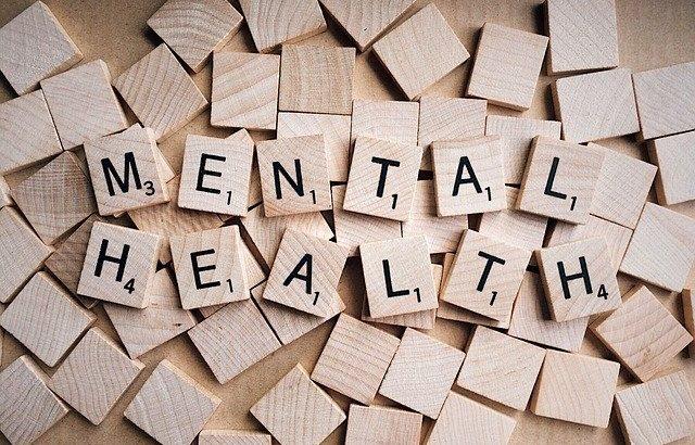 Einzelne Buchstaben auf Blöcken ergeben die Woerter Mental und Health