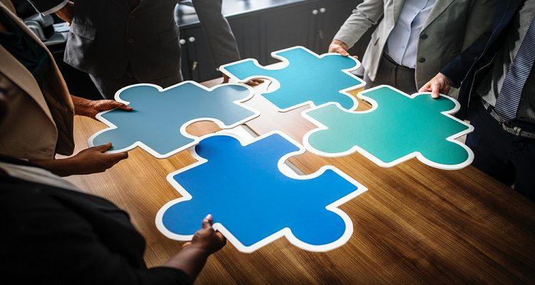 Business-People legen passende Puzzelteile zusammen
