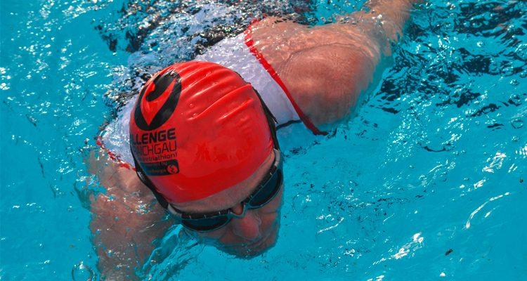 Mann mit Badekappe und Schwimmbrille schwimmt im Wasser der Schwimmhalle