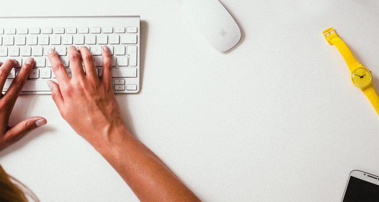 Nahaufnahme von Händen, die auf einer Tastatur tippen.