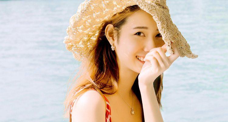Frau mit Sonnenhut am Wasser