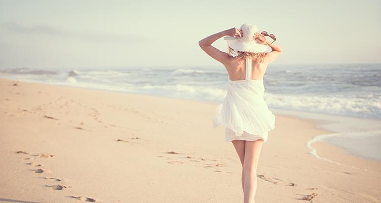 Frau spaziert am Strand.