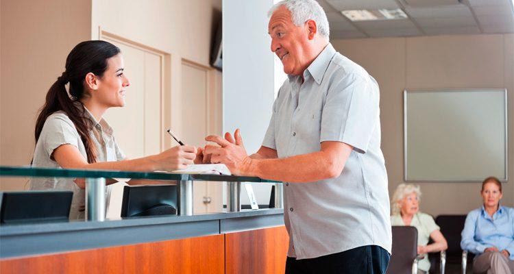 Arzthelferin und älterer Mann im Gespräch am Anmeldethresen einer Tagesklinik