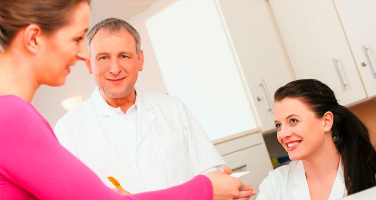 Frau am Thresen einer Arztpraxis