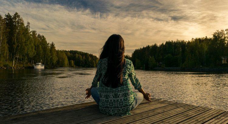 Frau sitzt am Wasser und meditiert