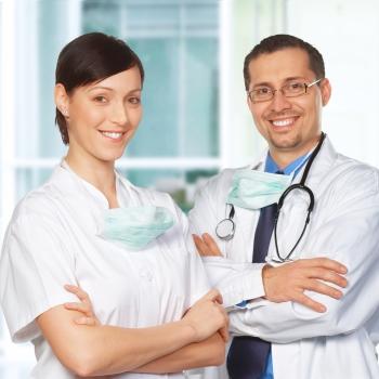Arzt und Ärzting lächeln in die Kamera.
